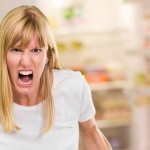 Portrait Of Angry Woman by a fridge full of food