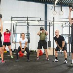 Group of young male and female athletes lifting kettlebells at cross training box